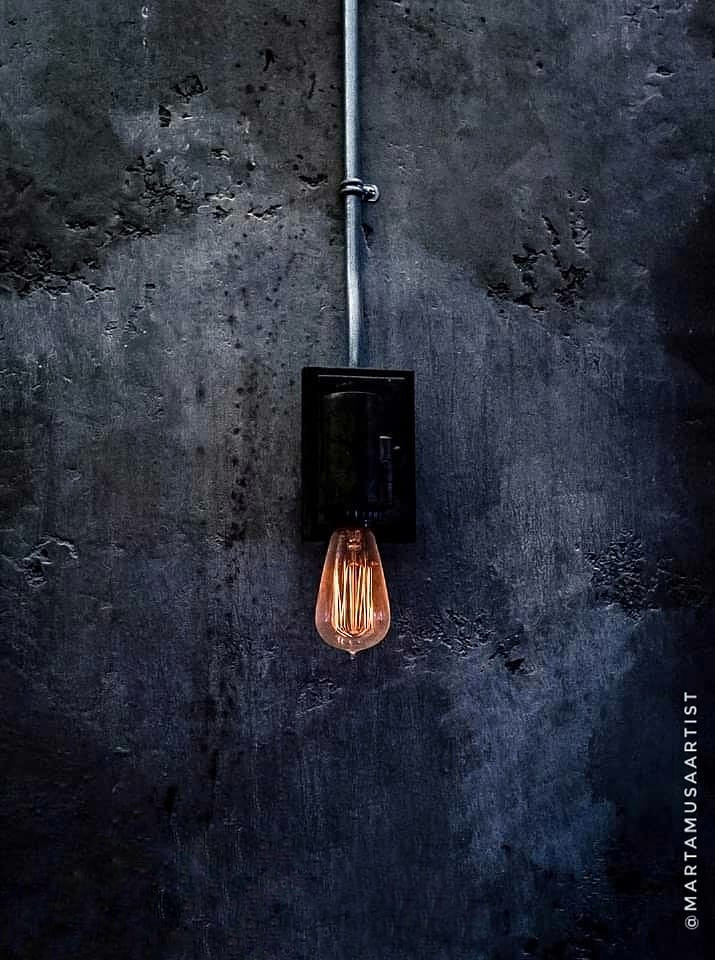 A photograph of a lit Edison Light bulb with its fixture adhered to a bluish grey concrete wall