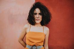 woman-wearing-an-orange-top-standing-bes