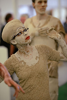 Simone, clothes, body, and hair wrap covered in clay. wearing striking makeup. doing mime.