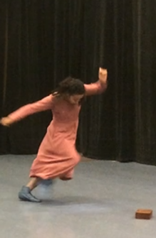 Still from a mime performance. Simone is off balance, small wooden box on the floor. black curtains