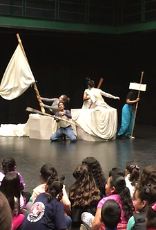 many children in foreground. Group of actors with flag, sticks, boxes and sheets making a boat