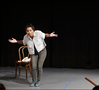 Video still. Simone bent forward and shrugging. phone sits on chair behind. Black curtains behind.