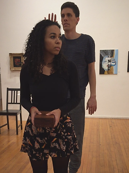In an art gallery.Simone in foreground face left, holding box. Man in back with 1 hand raised.