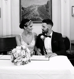 wedding couple at top table wearing pearl bridal headdress