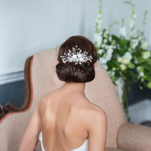 bride back view sat on pink chair with floral bridal hair comb