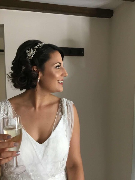 side view of bride with champagne wearing bespoke pearl wedding hair vine