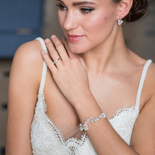 close up of bride on blue chair wearing pearl and crystal bridal bracelet