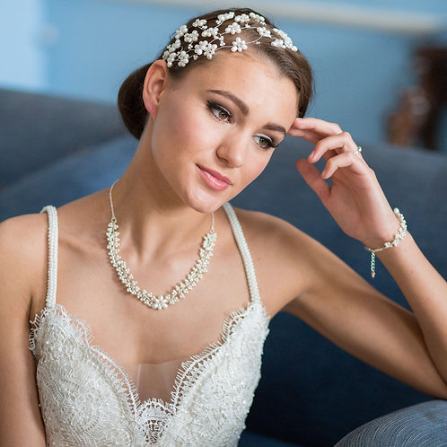 woman white dress blue chair pearl bridal necklace
