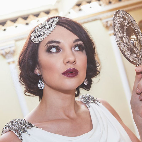 woman looking in mirror dark hair red lips white and crystal dress wearing crystal bridal headdress