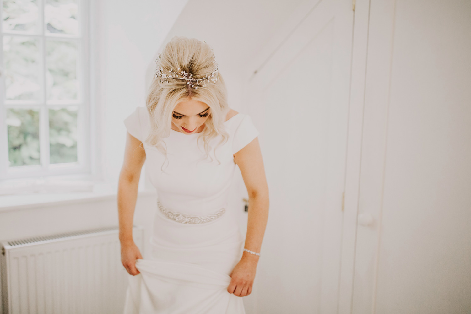 bride looking down at her dress with bridal hair vine