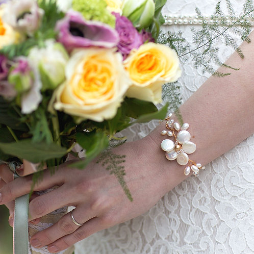 pink yellow flowers lace dress with arm wearing gold bridal pearl bracelet
