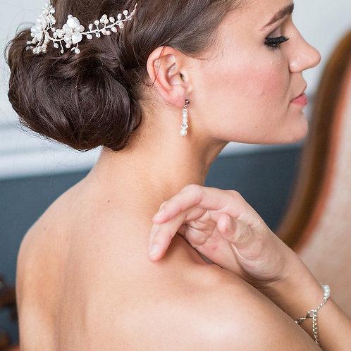 bride hand on shoulder brunette hair opal and crystal pearl wedding earrings