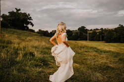 bride in field holding dress wearing bridal crystal hair vine