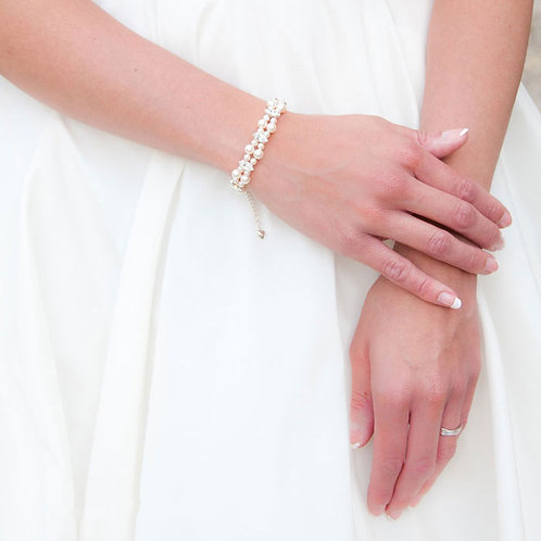 white dress arms holding with pearl and crystal double string bridal bracelet