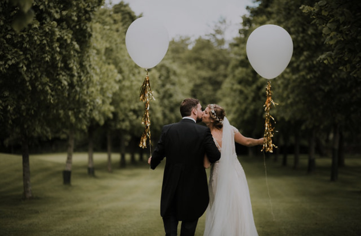 wedding couple with balloon wearing bridal hair garland