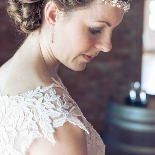 lace bridal dress bride looking down champagne and ivory wedding earrings