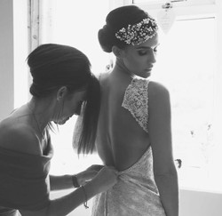 bride and mum doing up dress with pearl bridal head dress
