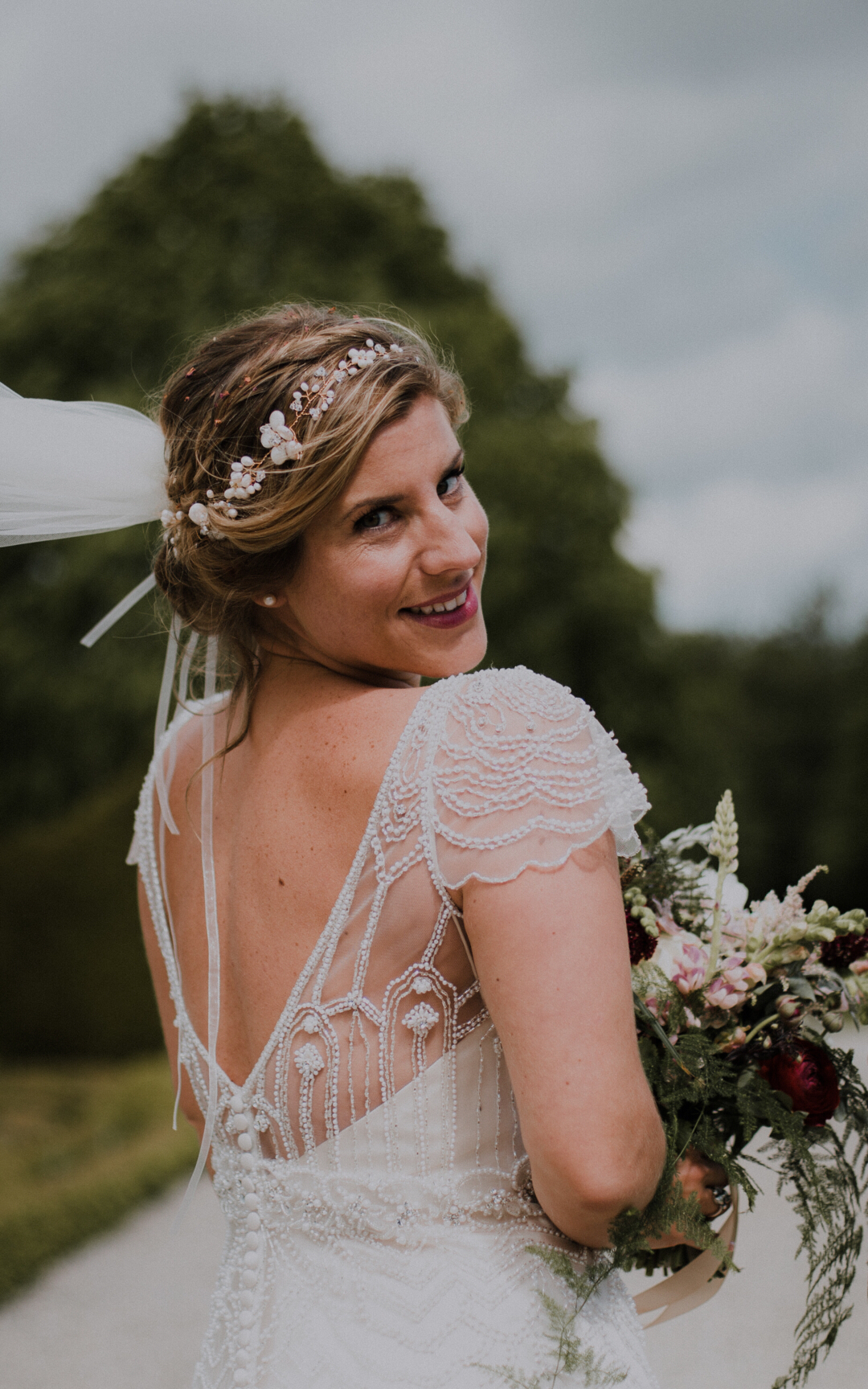 bride wearing ivory dress and pearl bridal hair garland