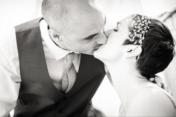 wedding couple kissing with bridal headdress being worn