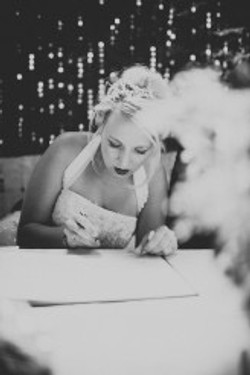 bride signing the register wearing crystal hair vine