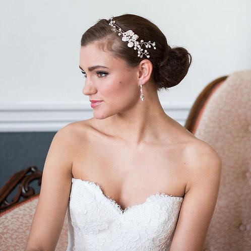 lady brunette hair white dress pink chair pearl flower headband