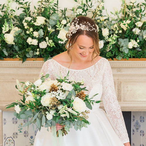 bride looking down with bridal hair vine and lots of green and white flowers