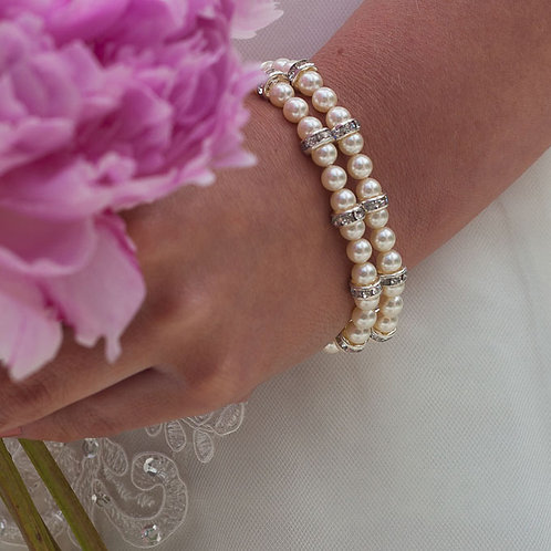 pink flowers white dress close up of double string pearl bridal bracelet