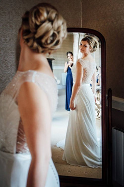 bride lookign in mirroe wearing bespoke bridal hair vine