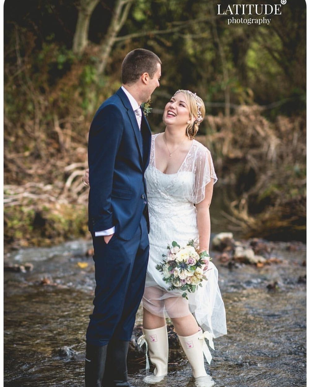 wedding couple in river with bride wearing white dress and pearl bridal headdress