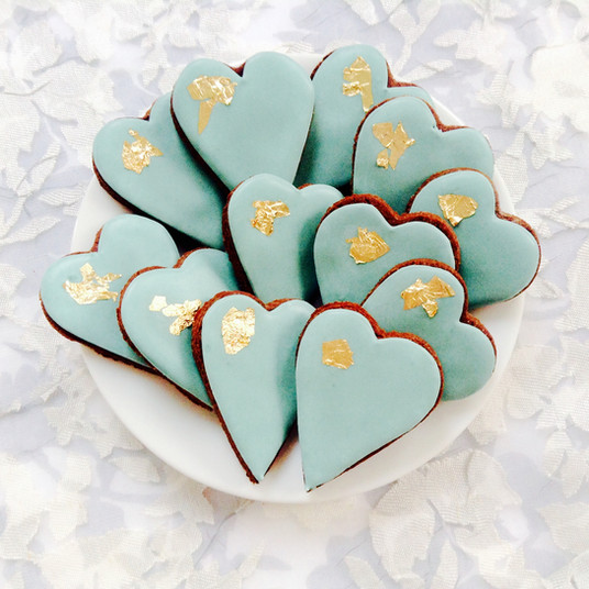 Pretty pale green heart iced biscuits with a touch of gold leaf