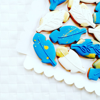 A box of pretty blue, white and gold feather iced biscuits