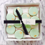 Mini pale green round iced biscuits with touch of gold leaf
