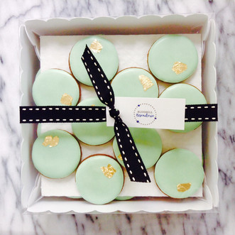 Mini pale green iced biscuits with a touch of gold leaf
