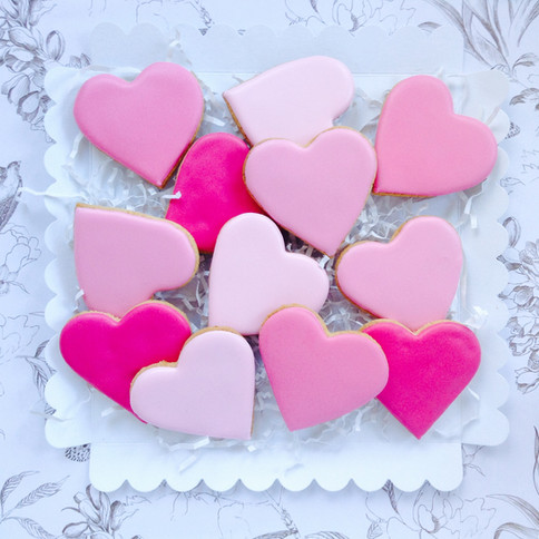 A dozen simple pink heart iced biscuits