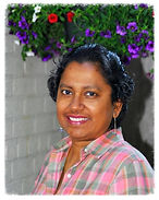 Kamini wearing a pink and gray plaid shirt, looking at the camera and smiling, with the background of a bush with purple and red flowers as the background