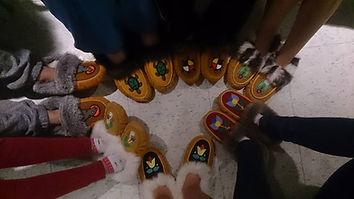 Photo des chaussures de plusieurs personnes en cercle. Tous portent des mocassins de couleur marron avec une fleur ou un animal différent sur chaque paire.