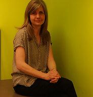 Erin porte un haut à motifs marron et est assise à côté d'une table qui se trouve contre un mur vert citron en arrière-plan