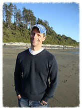 Darryl smiling,wearing a black crew-neck and light-blue cap and standing against a beach with black sand, as the back ground