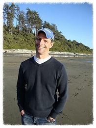 Darryl sourit, il porte un ras-du-cou noir et une casquette bleu ciel et se tient devant une plage de sable noir en arrière-plan