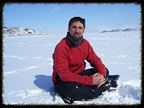 Chris sitting in the snow, wearing a red winter jacket and looking at the camera