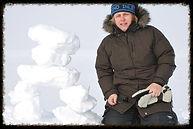 Joanne porte un chapeau bleu foncé et une veste d'hiver marron et se tient devant un arrière-plan enneigé