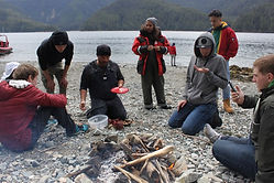 Group of people kneeling and surrounding a man-made camp fire. They are near a lake and are having lunch.