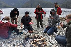 Un groupe de personnes sont à genoux autour d'un feu de camp. Ils sont près d'un lac et sont en train de diner.