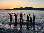 Silhouttes of people are making a YMCA sign with their hands, standing at a beach during a sunset.