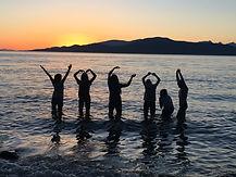 Des silhouettes humaines font le signe YMCA avec leurs mains et se tiennent debout à la plage au moment du coucher de soleil.