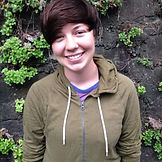 Jess smiling, wearing a brown hoodie, and standing against a natural backdrop with greenery