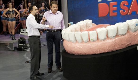 Dr. Arany Tunes, especialista em mau hálito, explicando como passar o fio dental no Domingão do Faustão