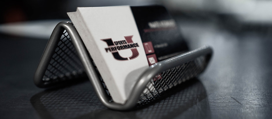 close up of business cards sitting in tray with sports performance U logo visible