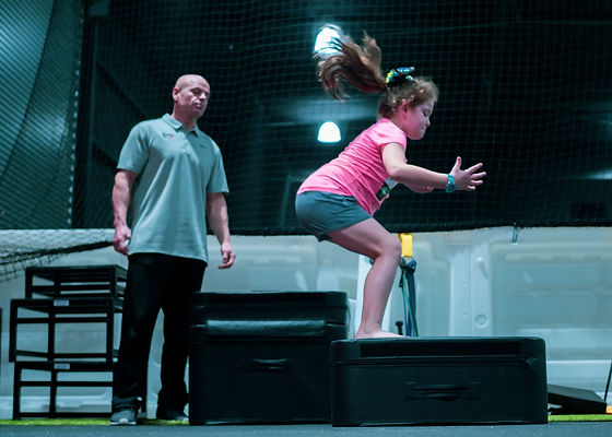 Coach watching female youth athlete land on top of 12 inch foam plyo box