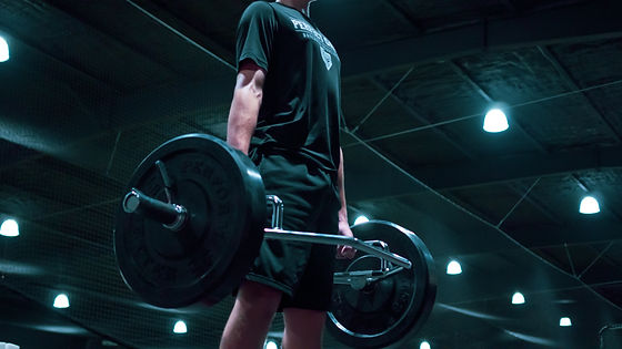 teenage athlete standing inside trapbar loaded with two 45lb. bumper plates